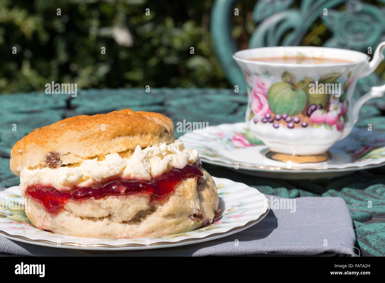 A fresh scone filled with whipped Cornish clotted cream and strawberry jam served on ornate antique bone china crockery - Stock Image