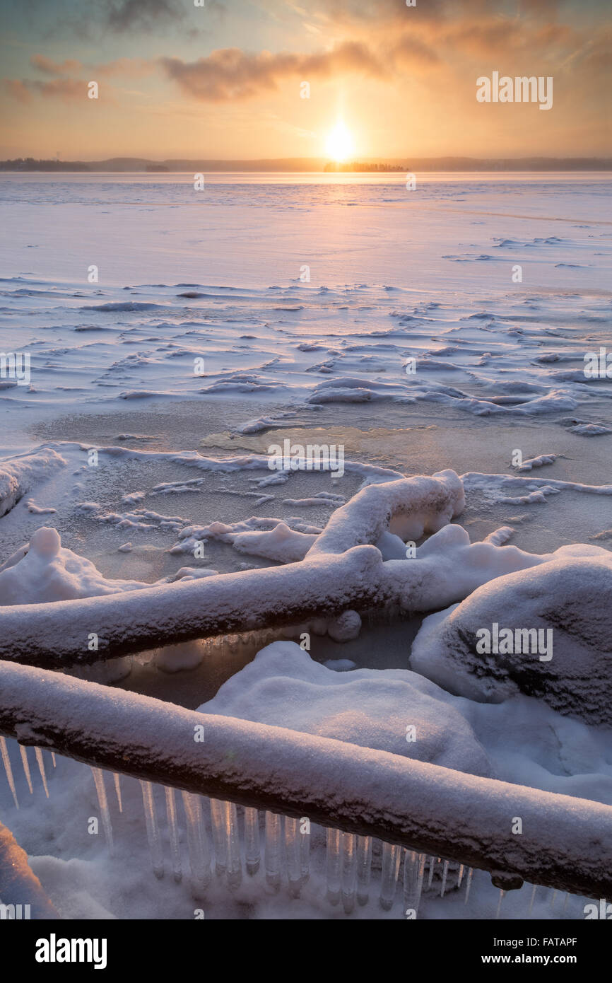 Sunrise at the frozen and snowy Lake Pyhäjärvi in Tampere, Finland, in the winter. - Stock Image