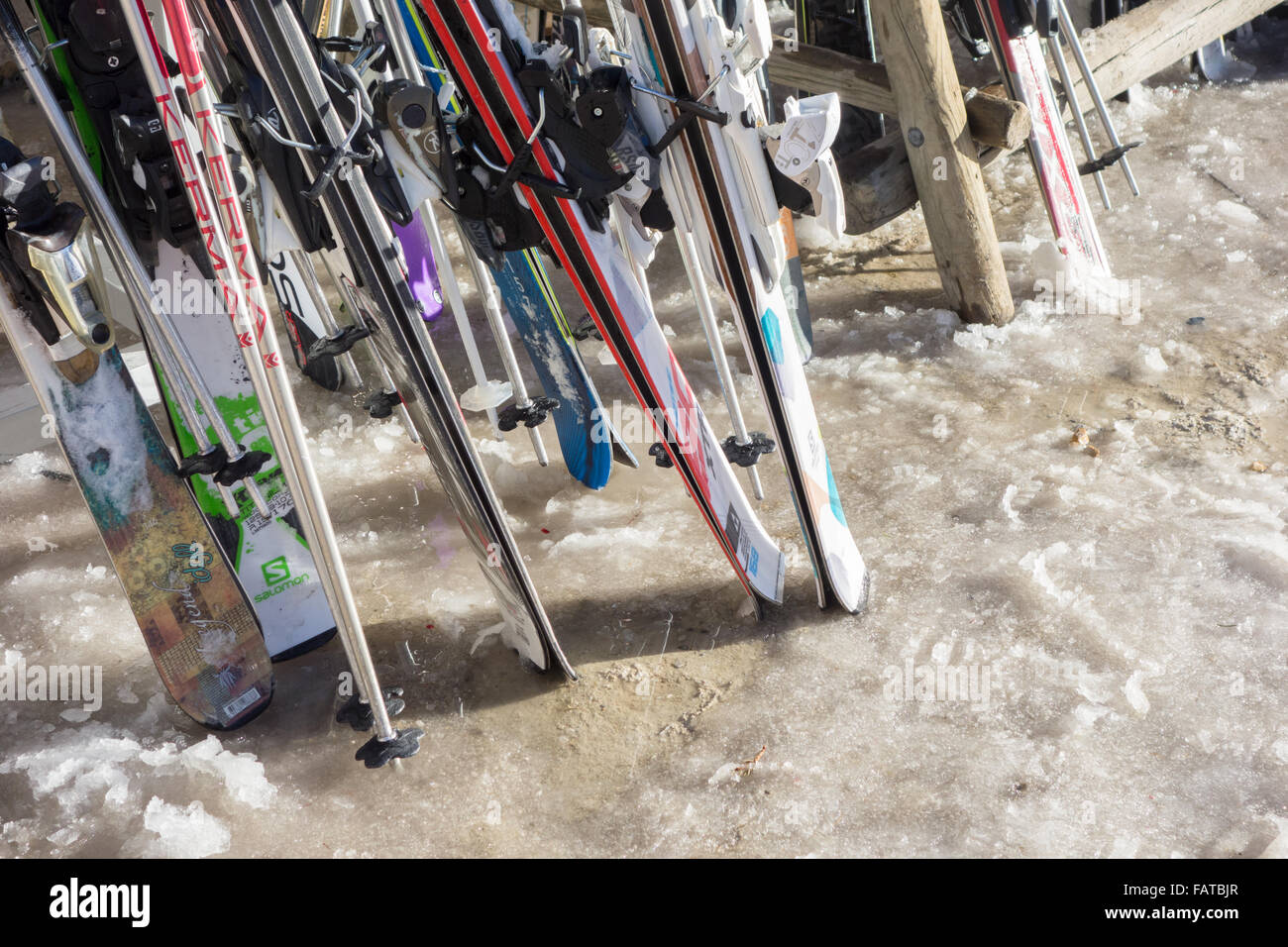skis in ski rack on melting snow during unseasonably warm weather - Courchevel, France - Stock Image