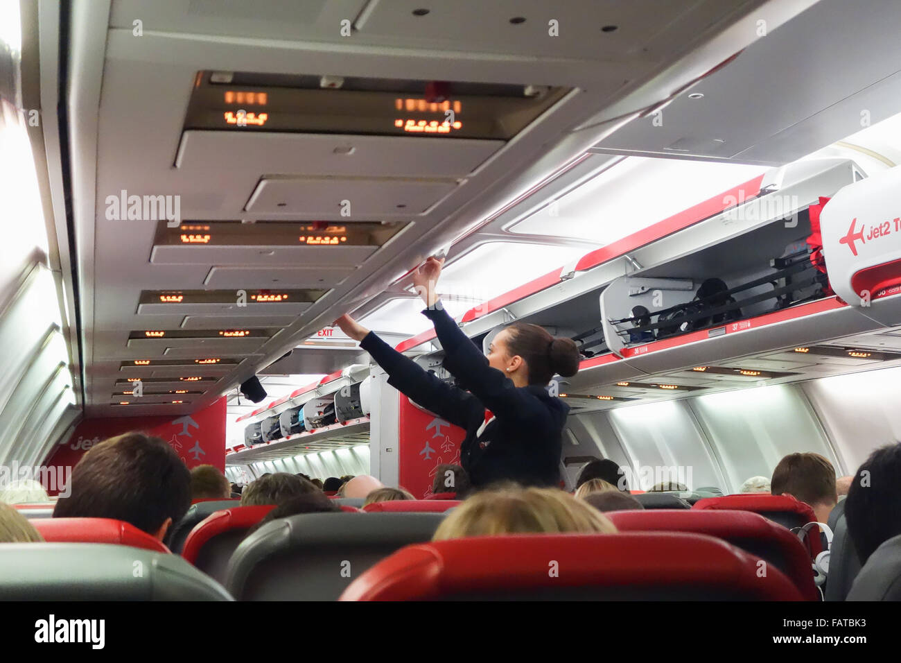 Female flight attendant checking and closing overhead luggage lockers on a Jet2 flight - Stock Image