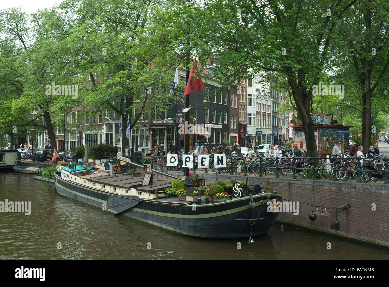 Old Amsterdam, Holland. House Boat / Barge Musem on a canal and street scene with bicycles and trees. - Stock Image