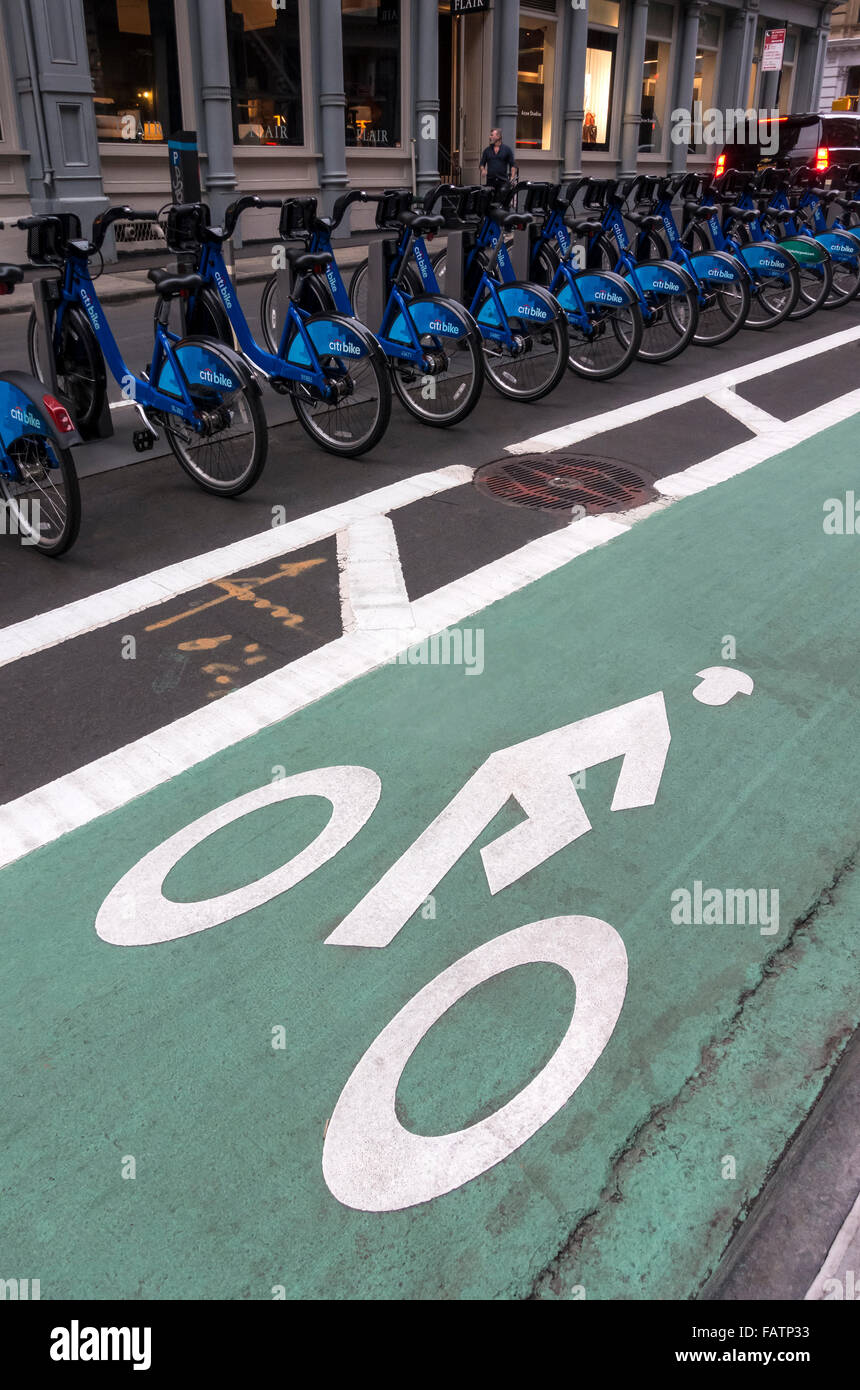 A bicycle path on a street in Soho in New York City next to a Citi Bike sharing station - Stock Image