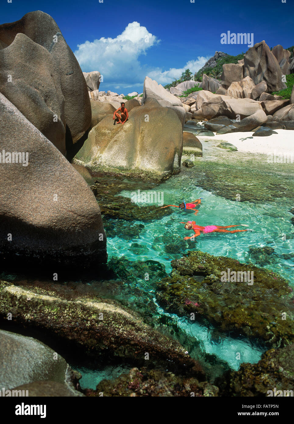 Tourists snorkeling in tide pools on La Digue Island in Seychelles - Stock Image