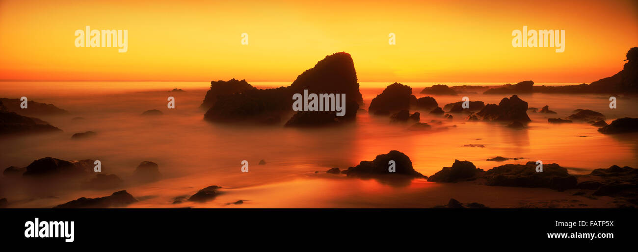Sunset skies painting rocks and sandy shore in Laguna Beach, California - Stock Image