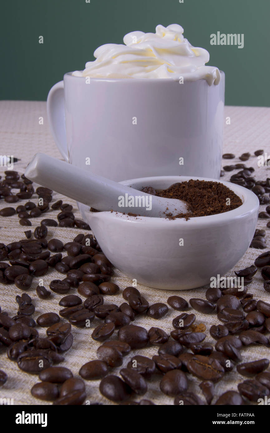 coffee cup with beans being ground with mortal and pestle - Stock Image