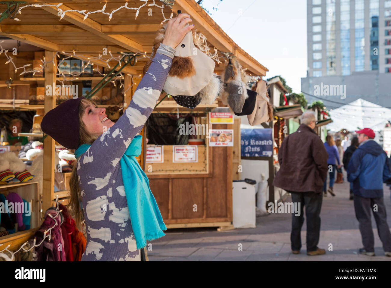 Denver, Colorado - A shopkeeper hangs up merchandise at the Denver Christkindl Market, a traditional German Christmas - Stock Image