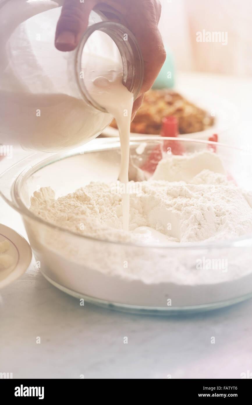 Pour sour milk into flour - Stock Image