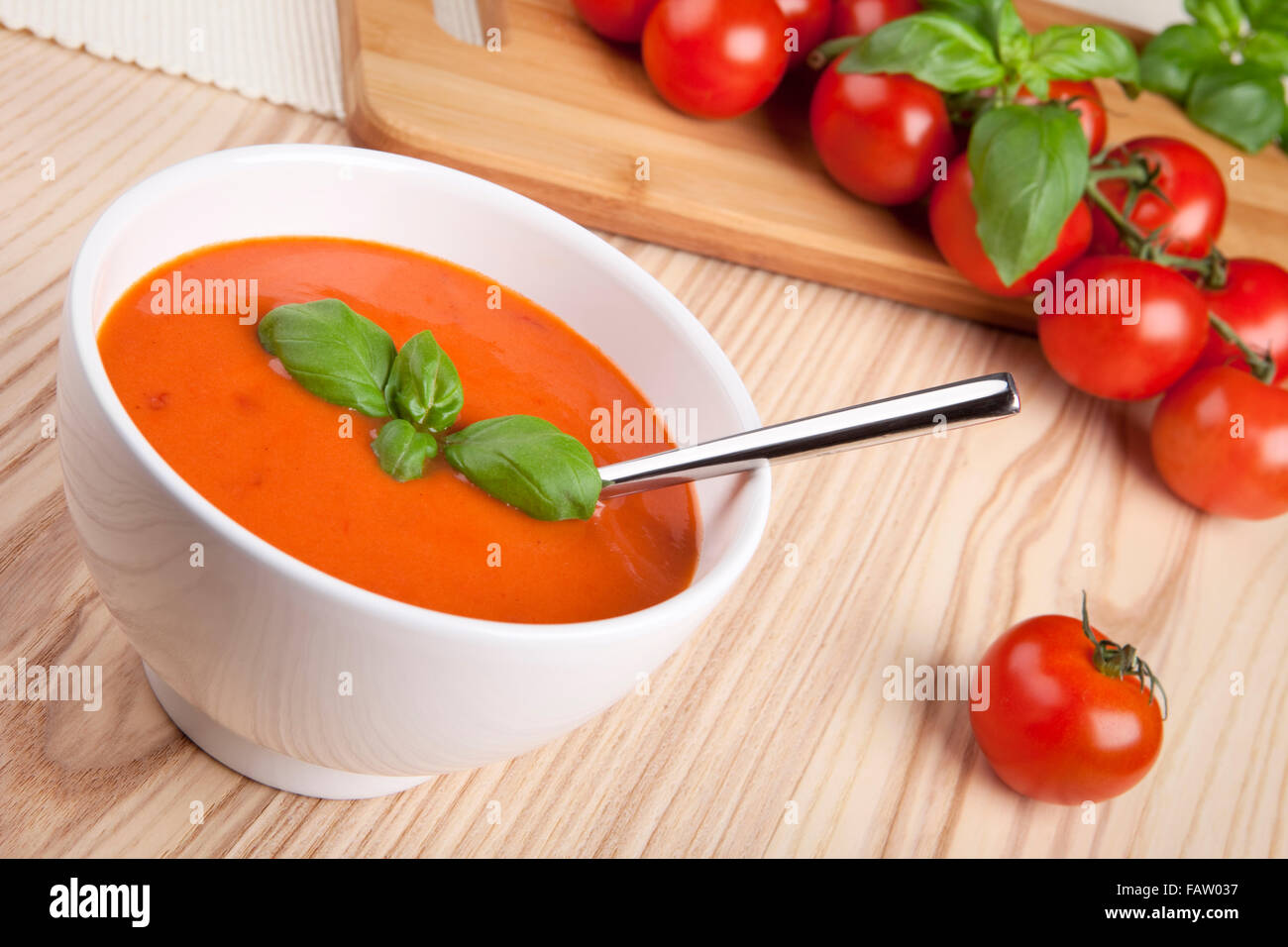 Tomato soup with basil in a bowl. - Stock Image