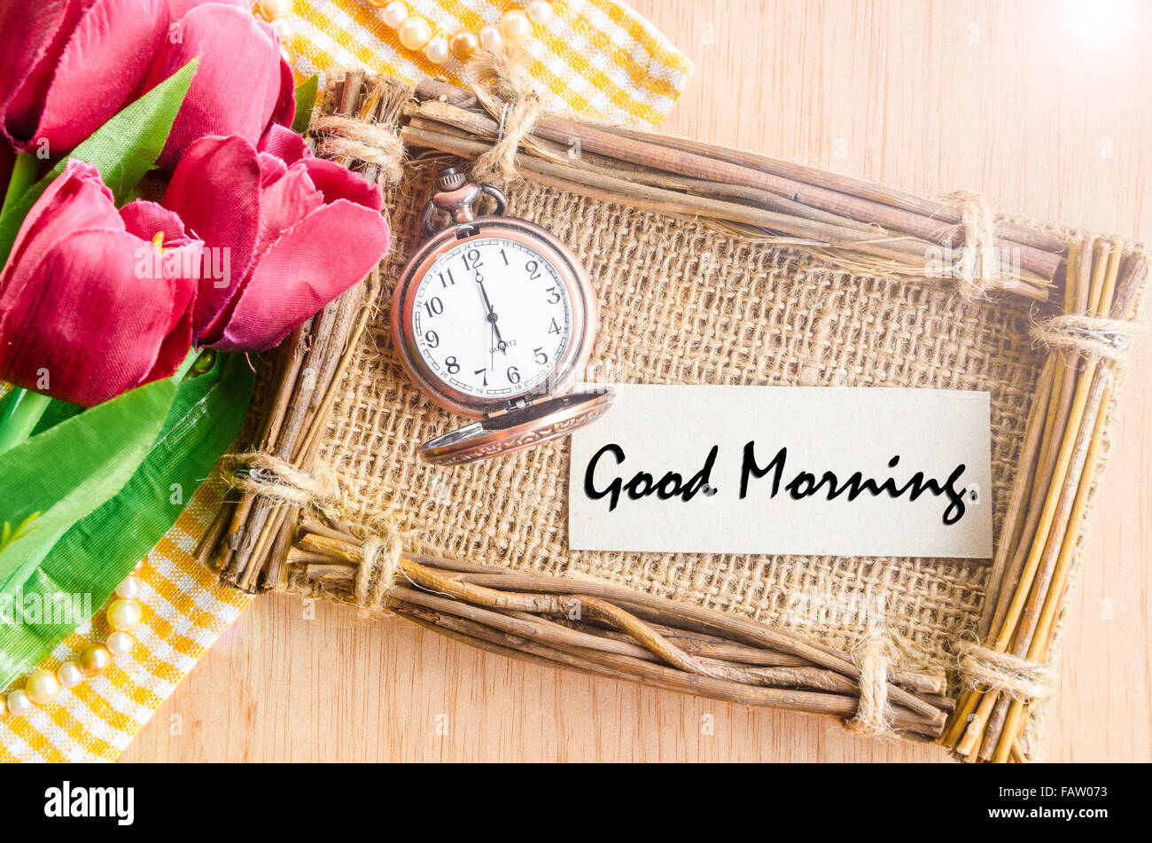 Good morning paper tag in sack photo frame and vintage alarm clock with red tulip on wooden background. - Stock Image