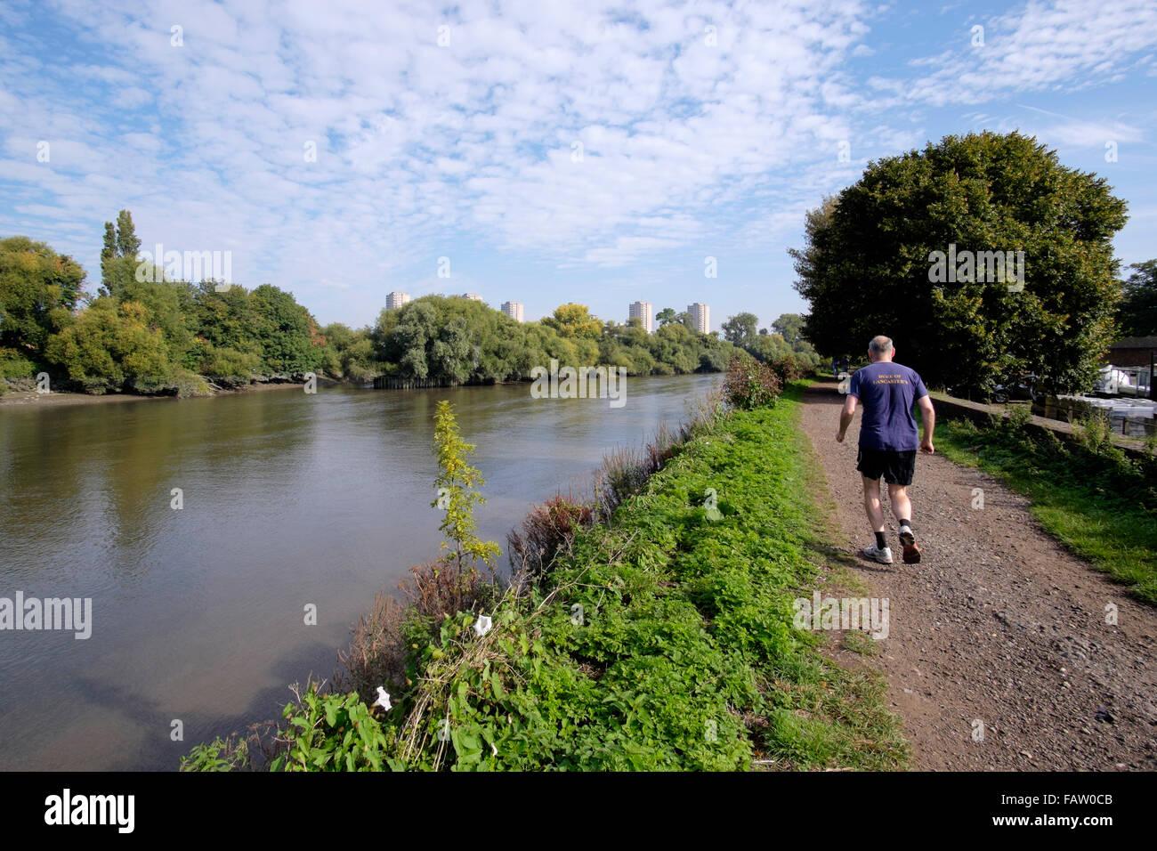 A senior man runs along the towpath towards Kew Bridge on the river Thames, London, England, UK - Stock Image