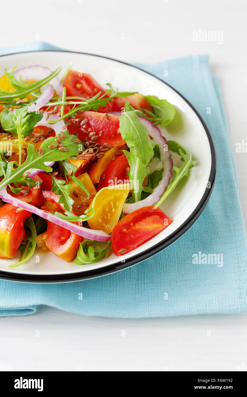 tomato salad with arugula in vintage plate, food closeup - Stock Image