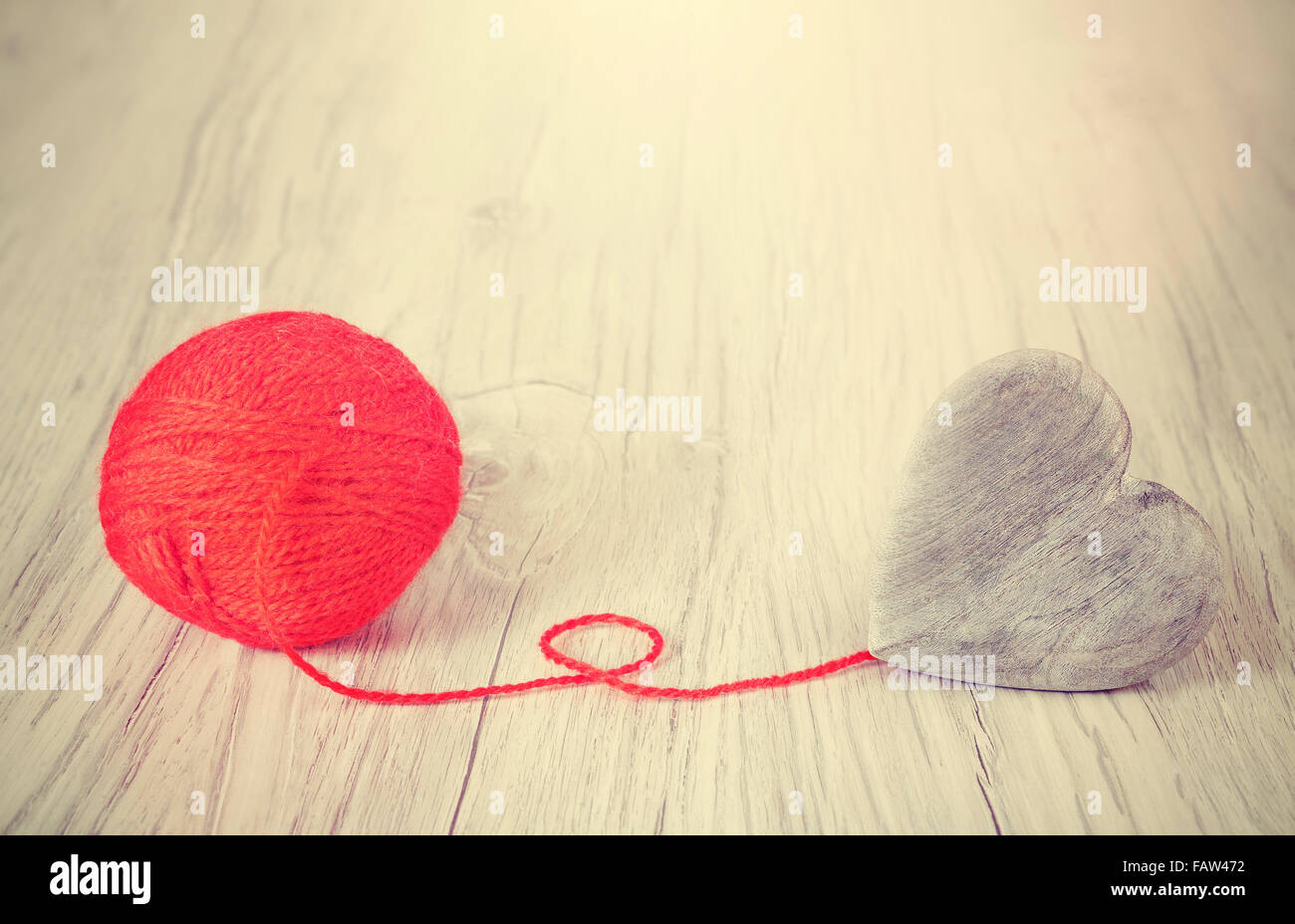 Wooden heart connected to red yarn, concept picture. - Stock Image