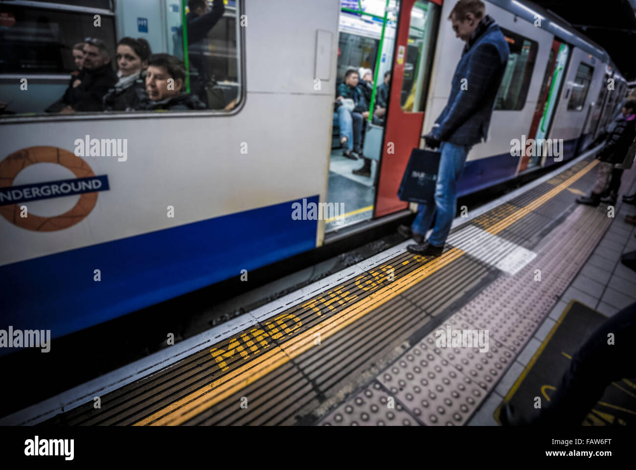MIND THE GAP warning. London underground station with tube train and platform Stock Photo
