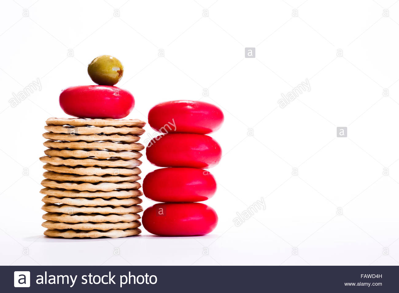 Stack of round cheeses with biscuits and olive on white background - Stock Image