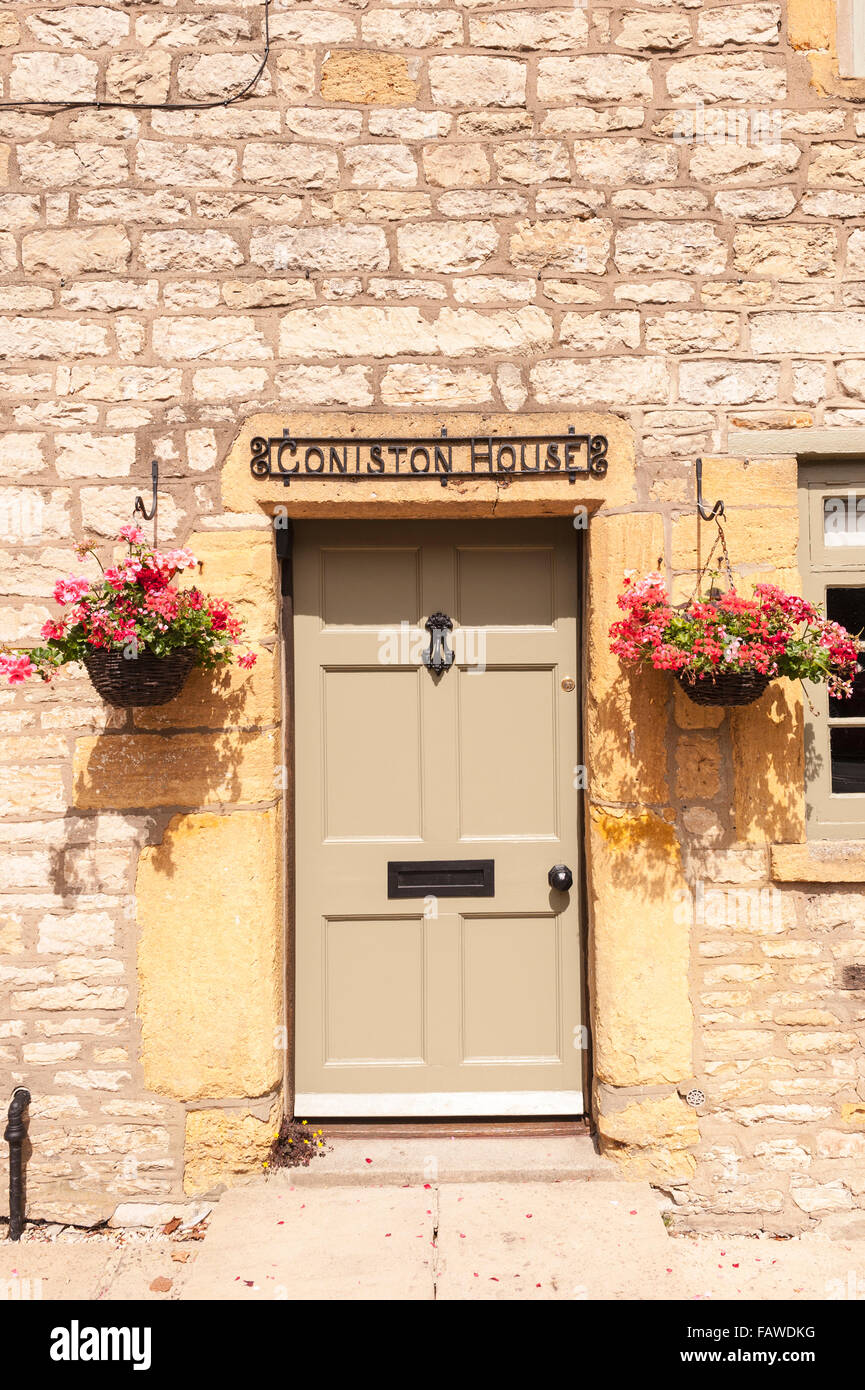 A pretty front door with hanging baskets at Stow-on-the-Wold , Cheltenham , Gloucestershire , England , Britain - Stock Image