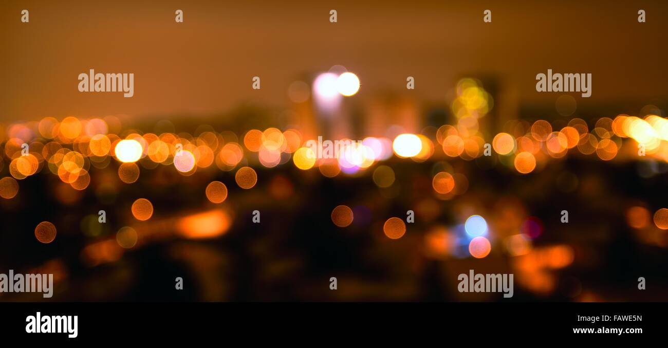 Abstract colorful defocused city lights with bokeh effects at night. Warm tone orange light background. - Stock Image