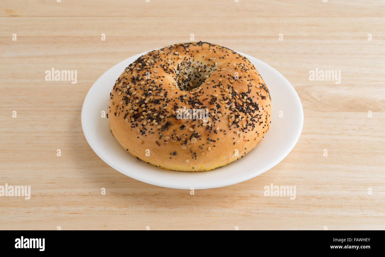 A bagel with several different types of seasonings on a white plate atop a wood table top. Stock Photo