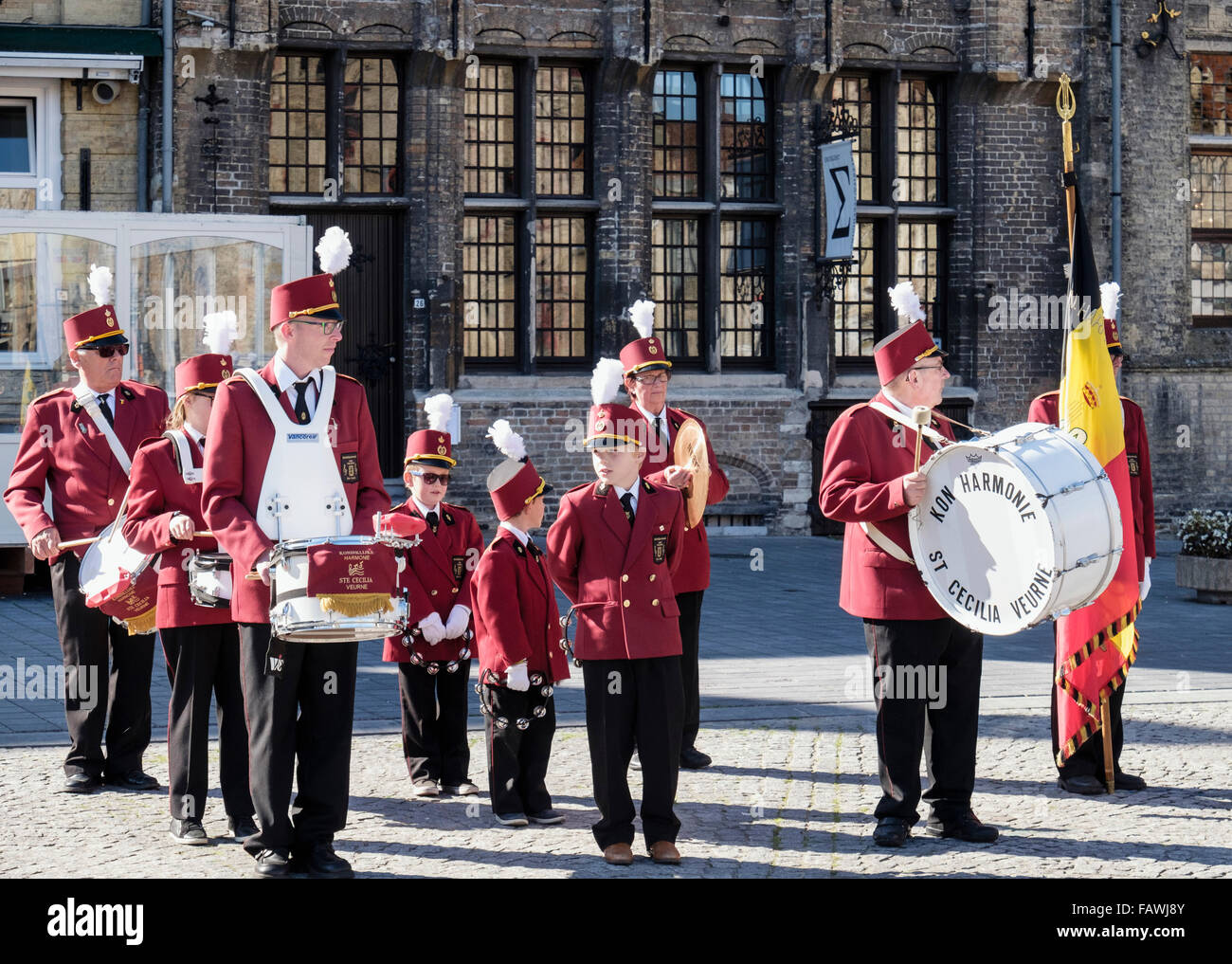 Men and young boys in the St Cecilia Kon Harmonie Band wait to play their instruments in Grote Markt Veurne Belgium - Stock Image