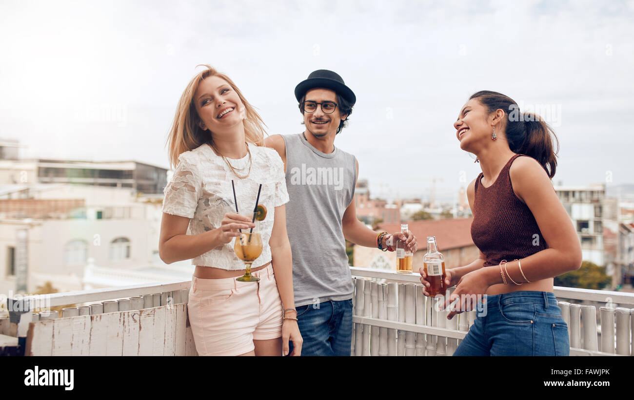 Group of happy young people standing together with drinks. Mixed race friends having rooftop party. Stock Photo
