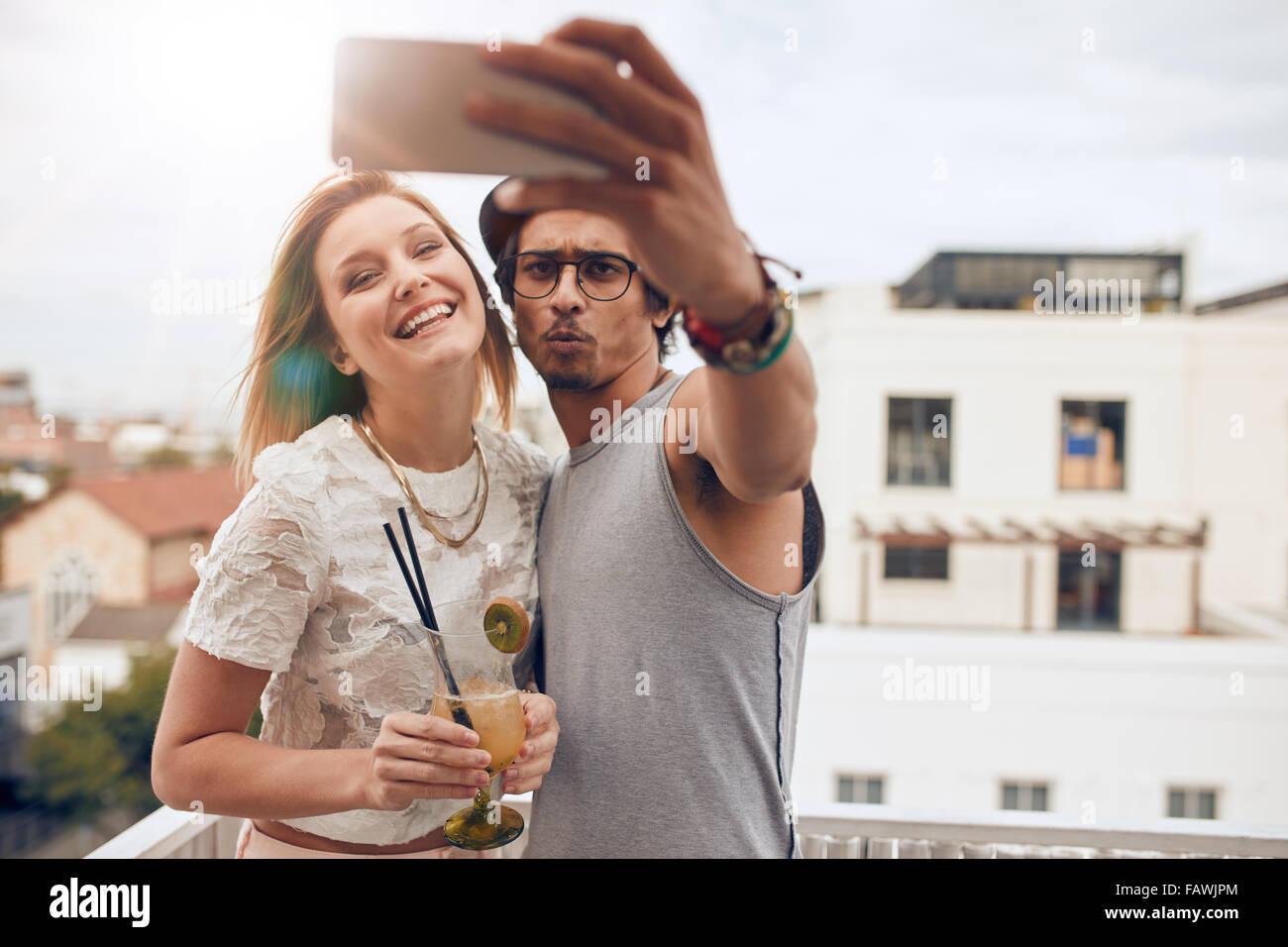 Two young friends taking a selfie on rooftop. Man holding smart phone and taking self portrait with woman holding - Stock Image