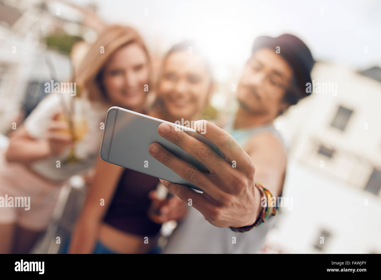 Young friends in a party taking self portrait with their smart phone. Focus on mobile phone in man's hand. - Stock Image