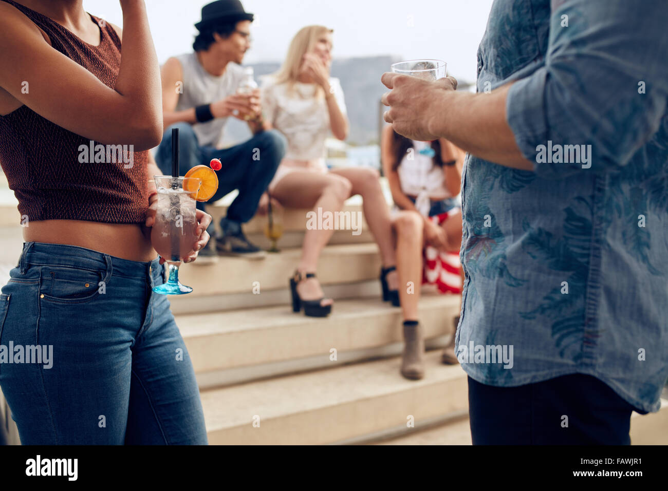 Cropped shot of a couple holding cocktails glasses while three people talking to each other in the background. Young - Stock Image