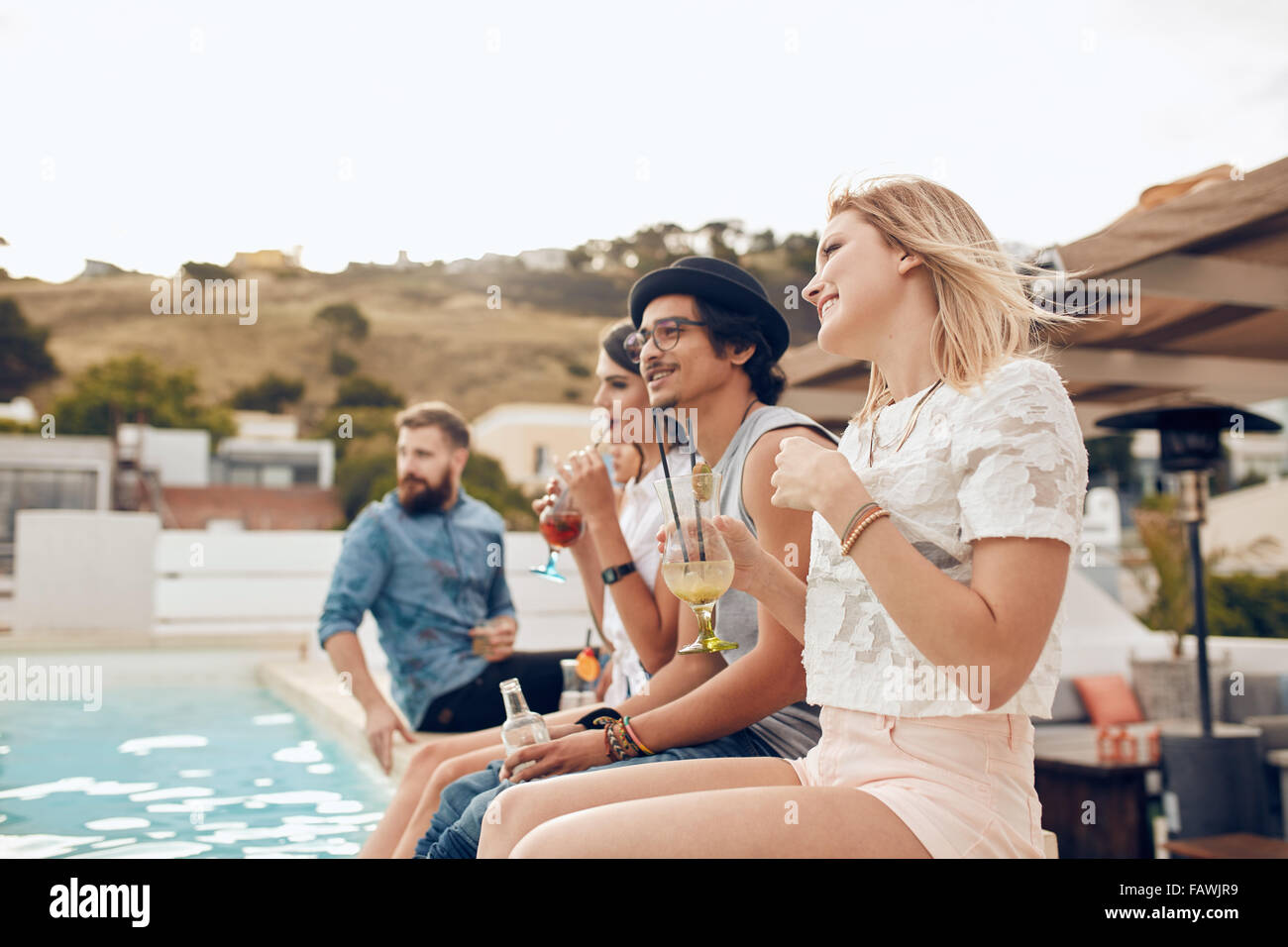 Happy young friends sitting by the pool having cocktail. Young people relaxing by the swimming pool with their feet - Stock Image