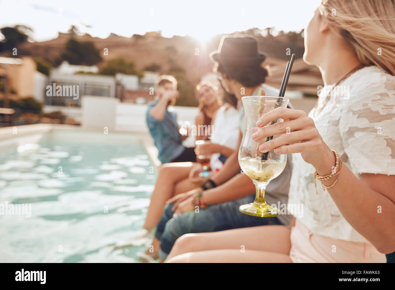 Woman holding a cocktail glass while sitting on the edge of swimming pool with friends. Young people enjoying a - Stock Image