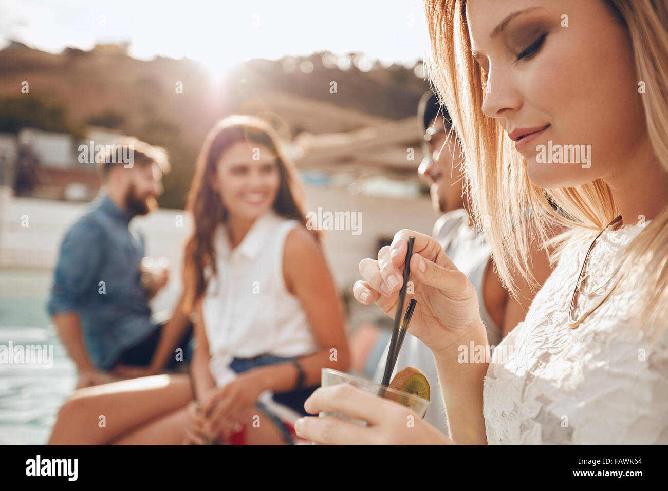 Close up shot of young woman having a drink while her friends sitting in background. Young people having a party - Stock Image