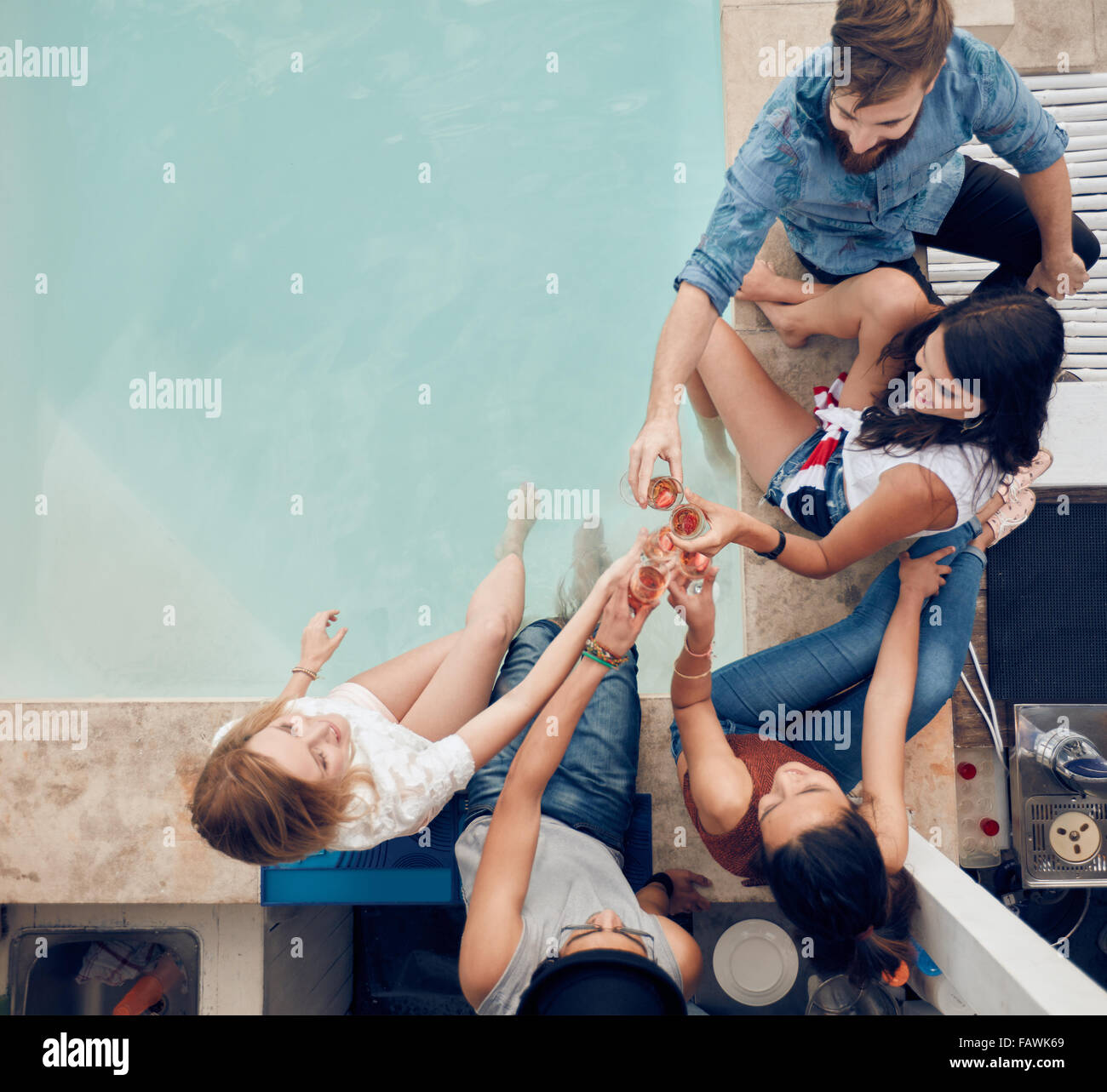 Top view of group of friends toasting at party by a swimming pool. High angle shot of young people sitting by the - Stock Image