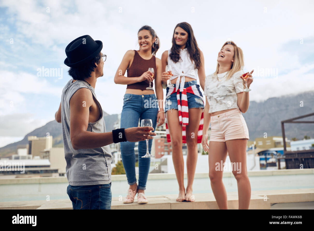 Portrait of happy young friends partying by the swimming pool. Young men and women enjoying a pool party with drinks. - Stock Image