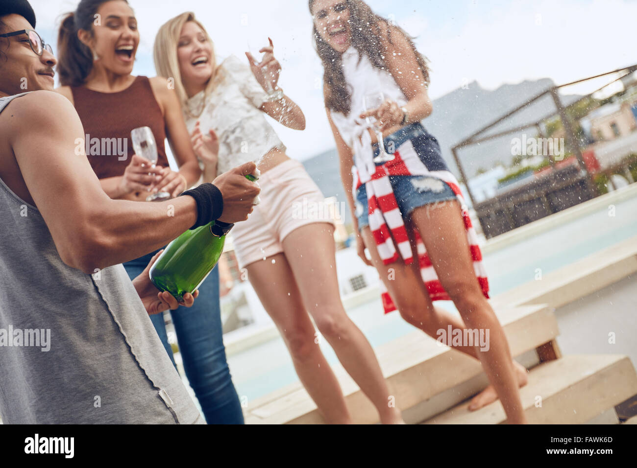 Party image of young man opening a bottle of champagne. Women standing by a swimming pool holding glasses and laughing. - Stock Image