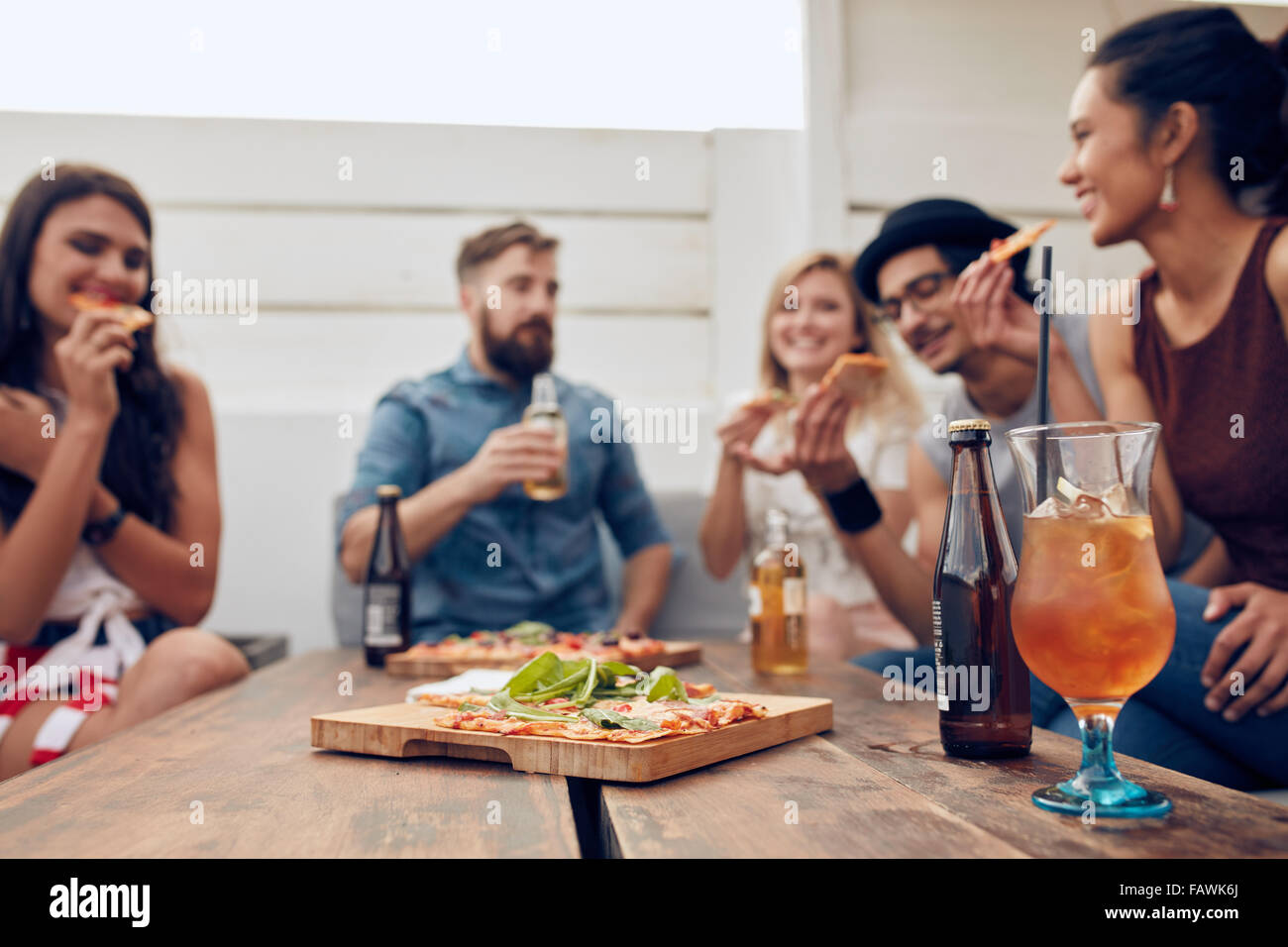 Group of multi-ethnic friends enjoying pizza and beer in party. Young people having a party. Focus on pizza and Stock Photo