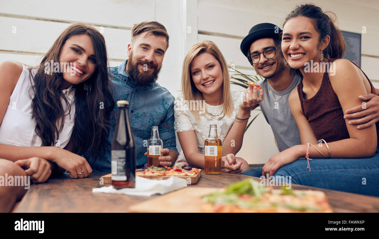 Group portrait of young friends gathered around the table at a rooftop party. Multiracial young people looking at - Stock Image