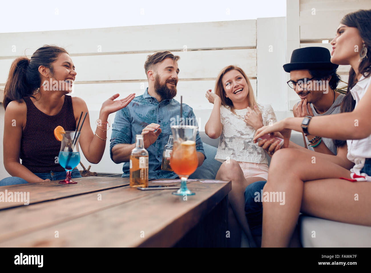 Portrait of happy young people sitting together and laughing. Multiracial friends enjoying at a party with cocktails Stock Photo