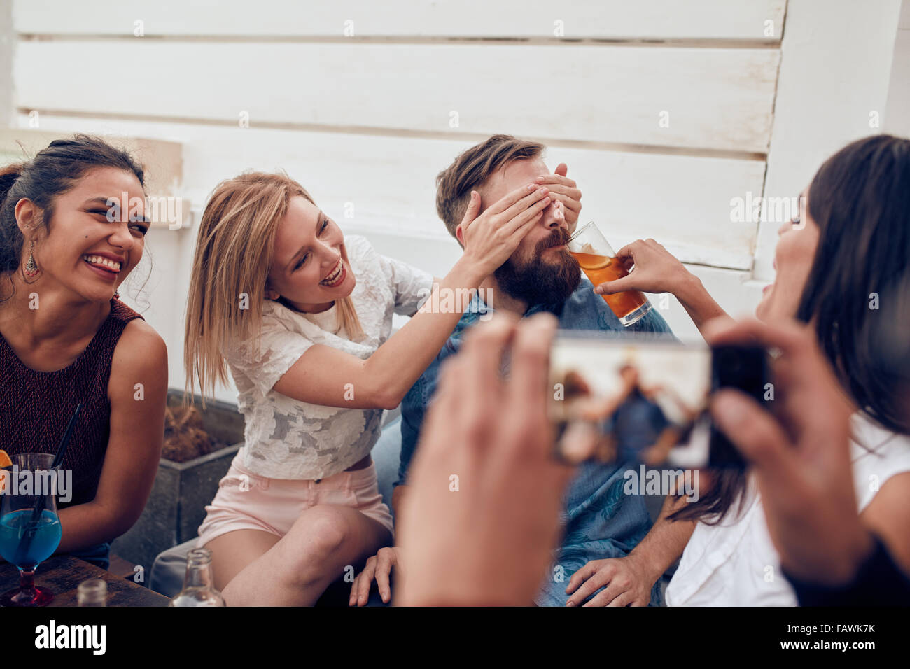 Young friends having fun at party being photographed with mobile phone. Young people sitting together enjoying party - Stock Image