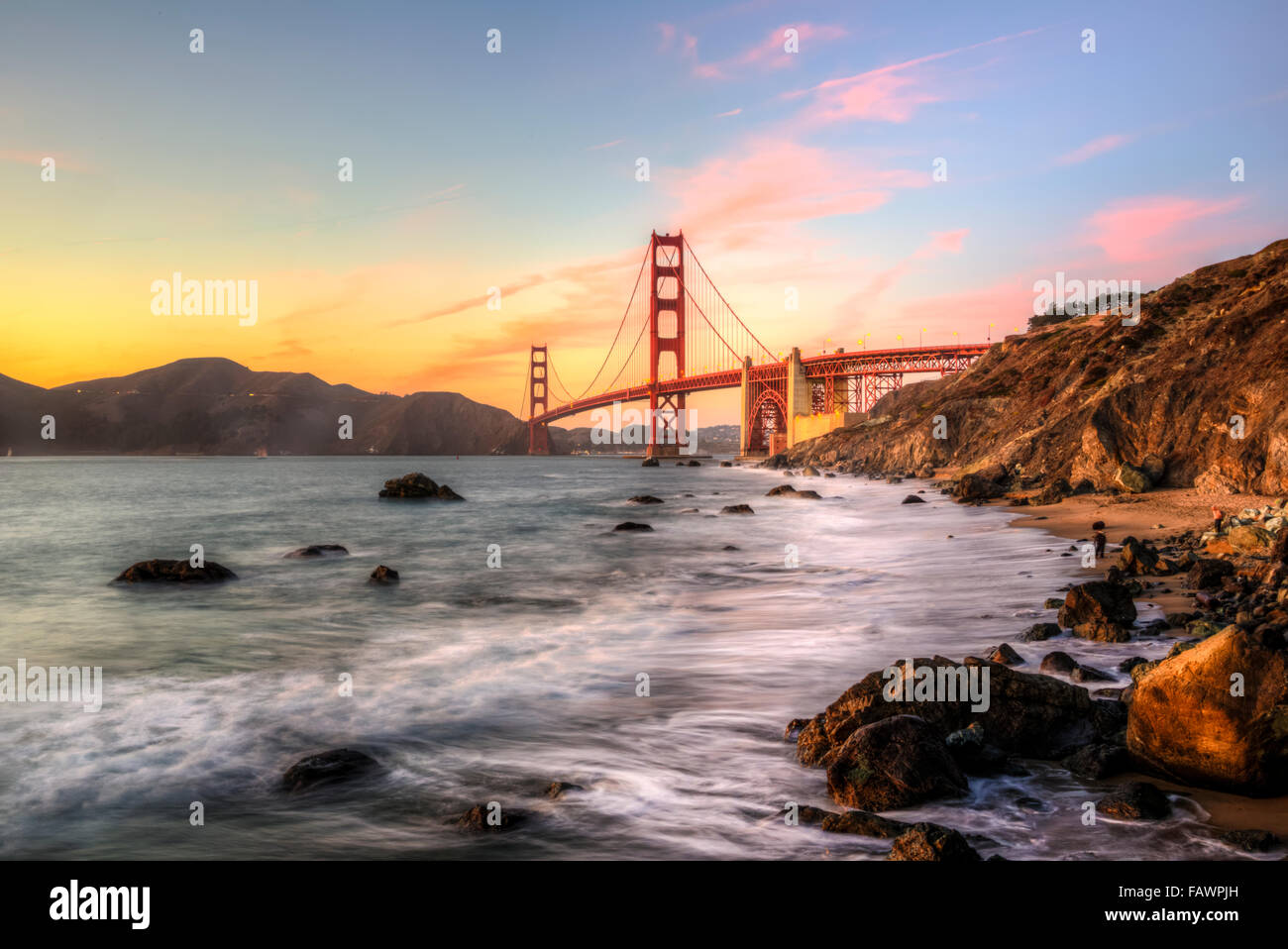 Golden Gate Bridge, Marshall's beach, sunset, rocky coast, San Francisco, USA - Stock Image