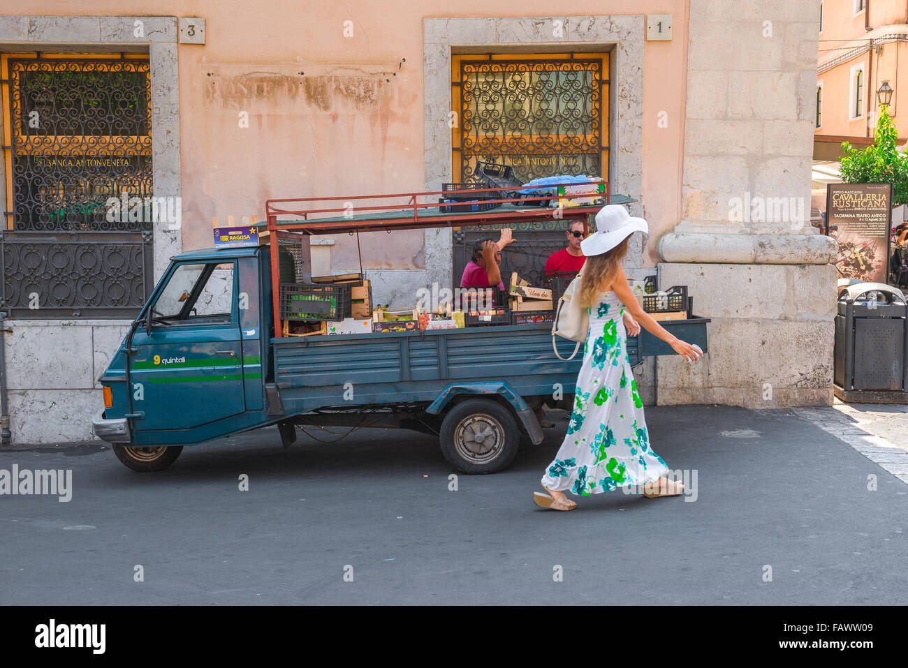 Men looking woman, view of two men looking at a young woman in a long summer dress as she walks past a fruit vendors' Stock Photo