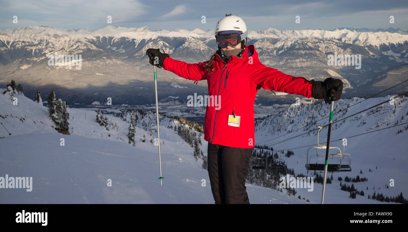 A skier on a mountain top with a view of the Canadian Rocky mountains, Banff national park; Alberta, Canada - Stock Image