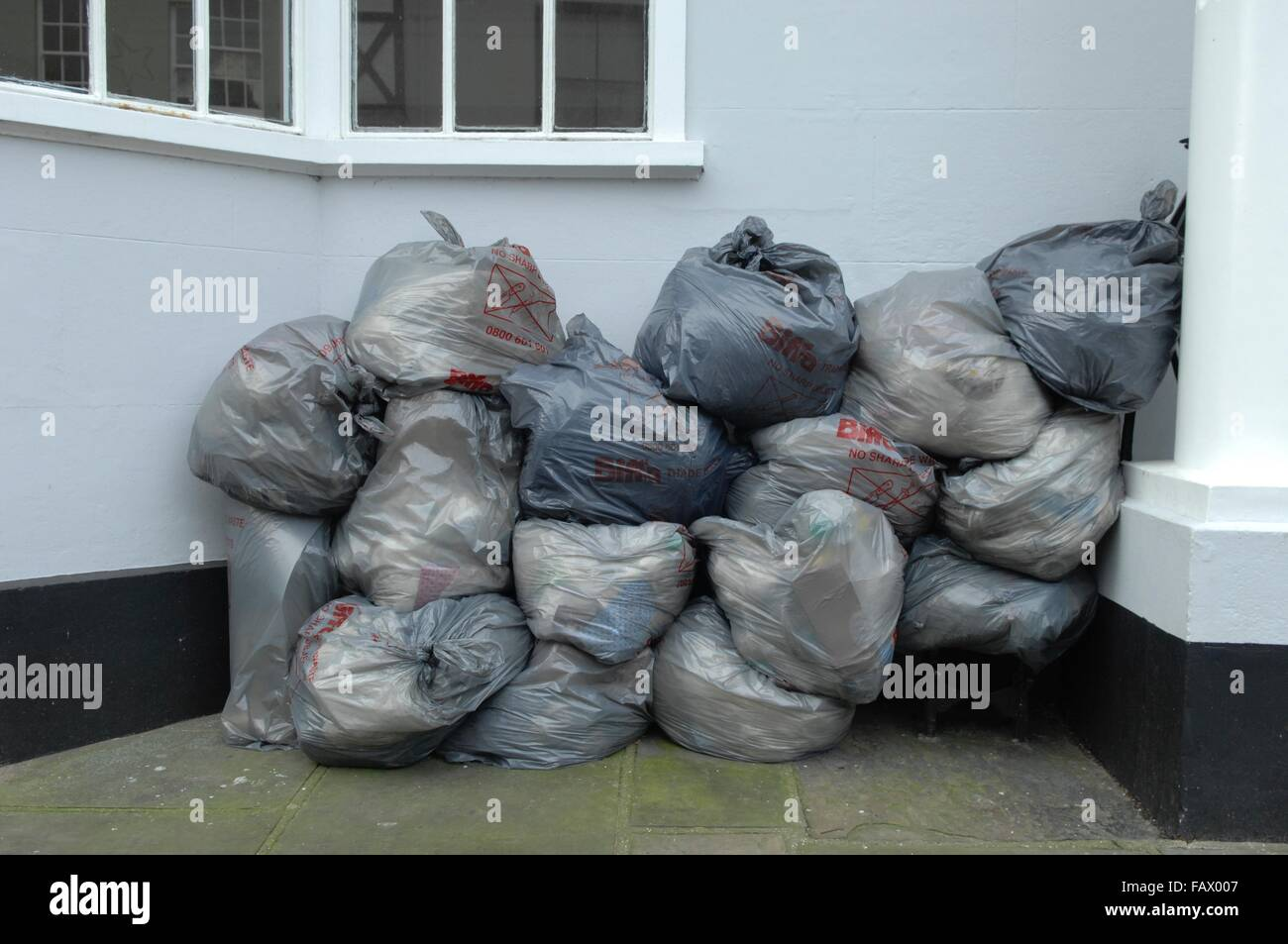 A back street in malaga with rubbish bags waiting to be picked up from the rubbish men - Stock Image