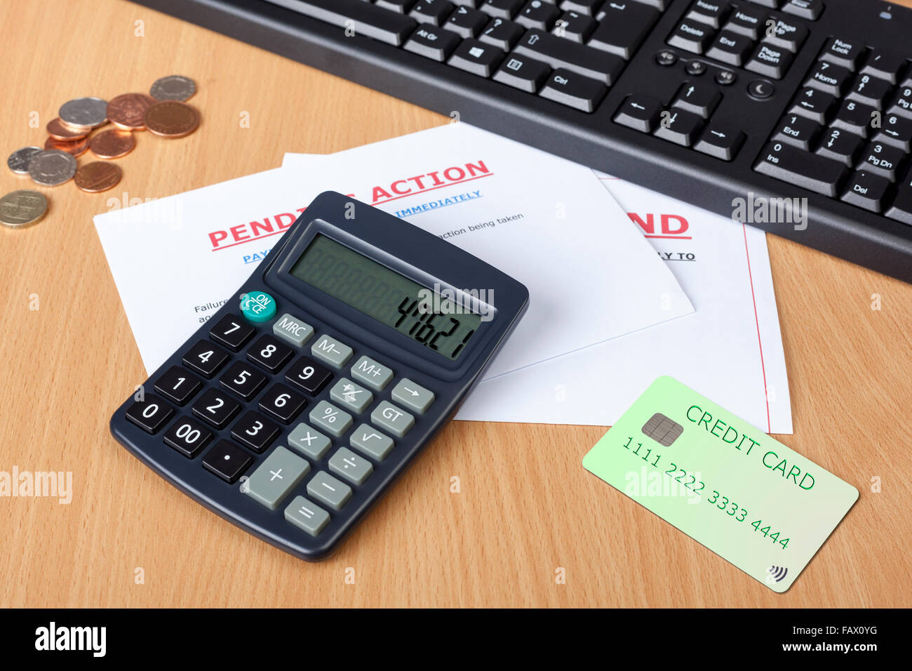Desk showing final demands with credit card and a calculator along side a computer keyboard amd some cash - Stock Image