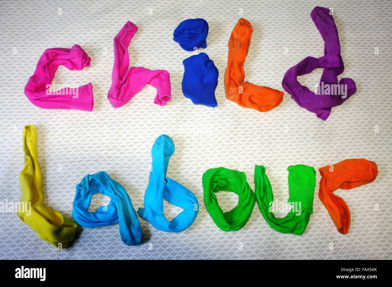 The words child labour made out of colourful socks laying on a duvet cover. - Stock Image