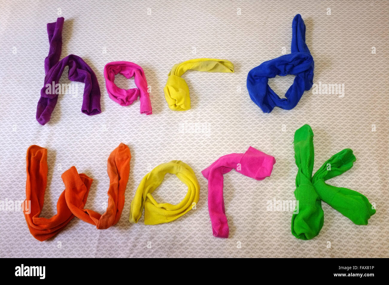 The words hard work made out of colourful socks laying on a duvet cover. - Stock Image