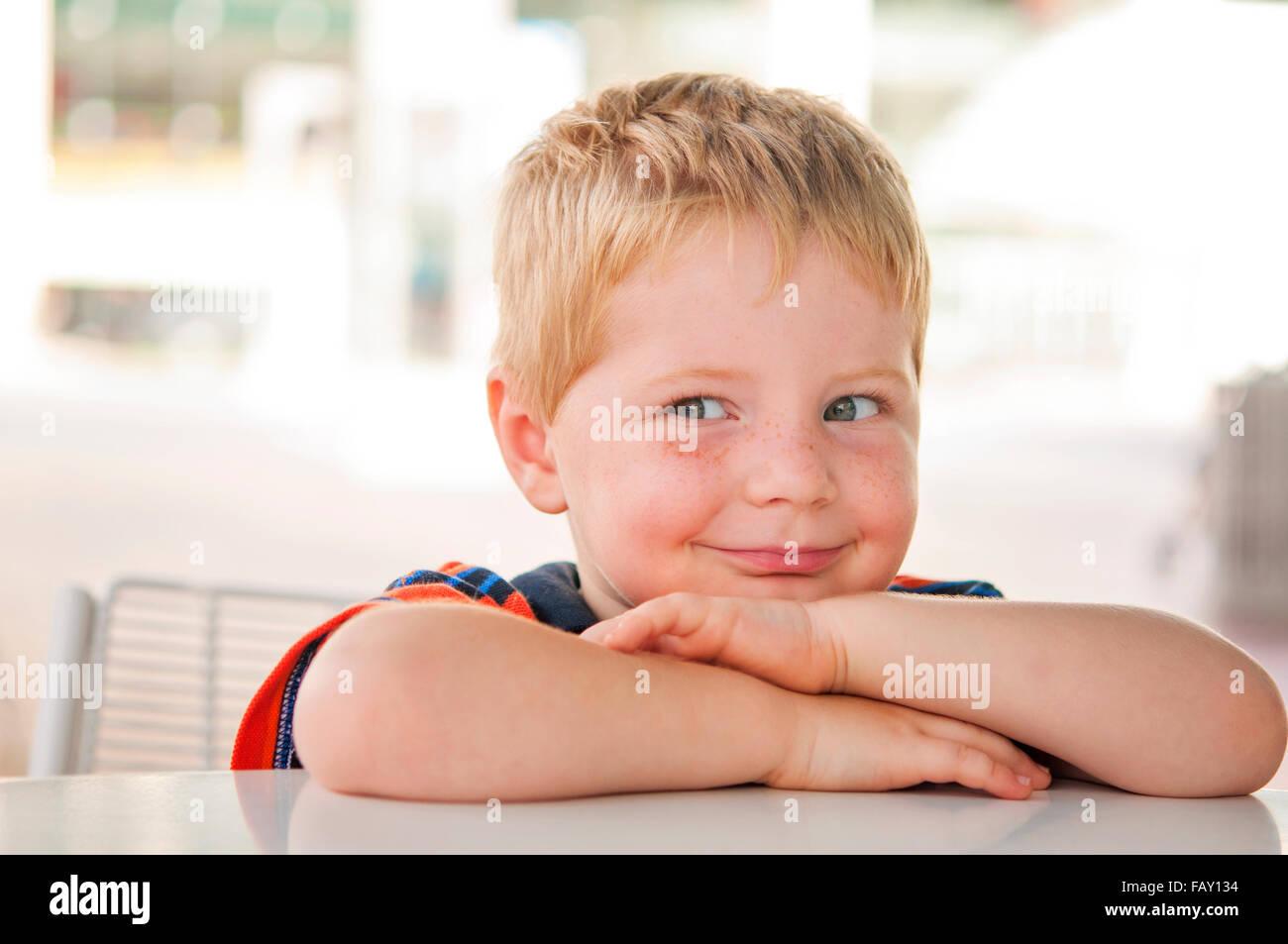 Mischievous smiling boy - Stock Image