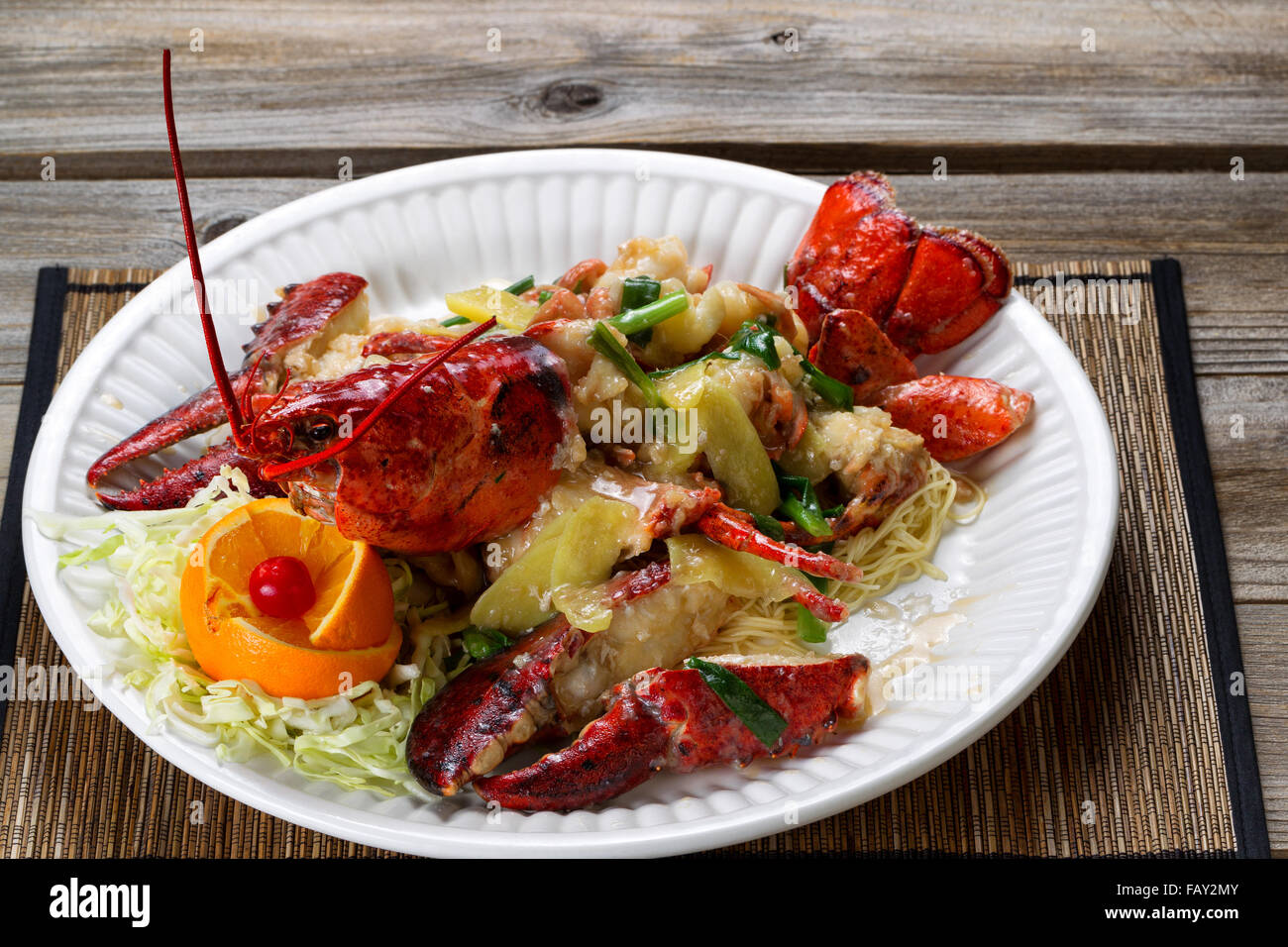Close up front view of a freshly cooked whole Maine lobster covered with herbs, onions, and sauce on white plate. - Stock Image