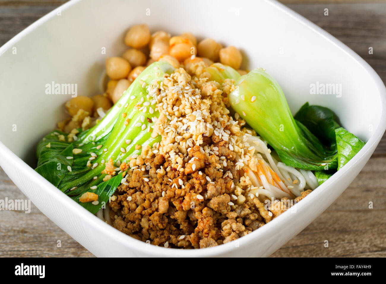 Close up front view of crispy spicy chicken with noodles and bok choy in white bowl. Selective focus in middle of - Stock Image