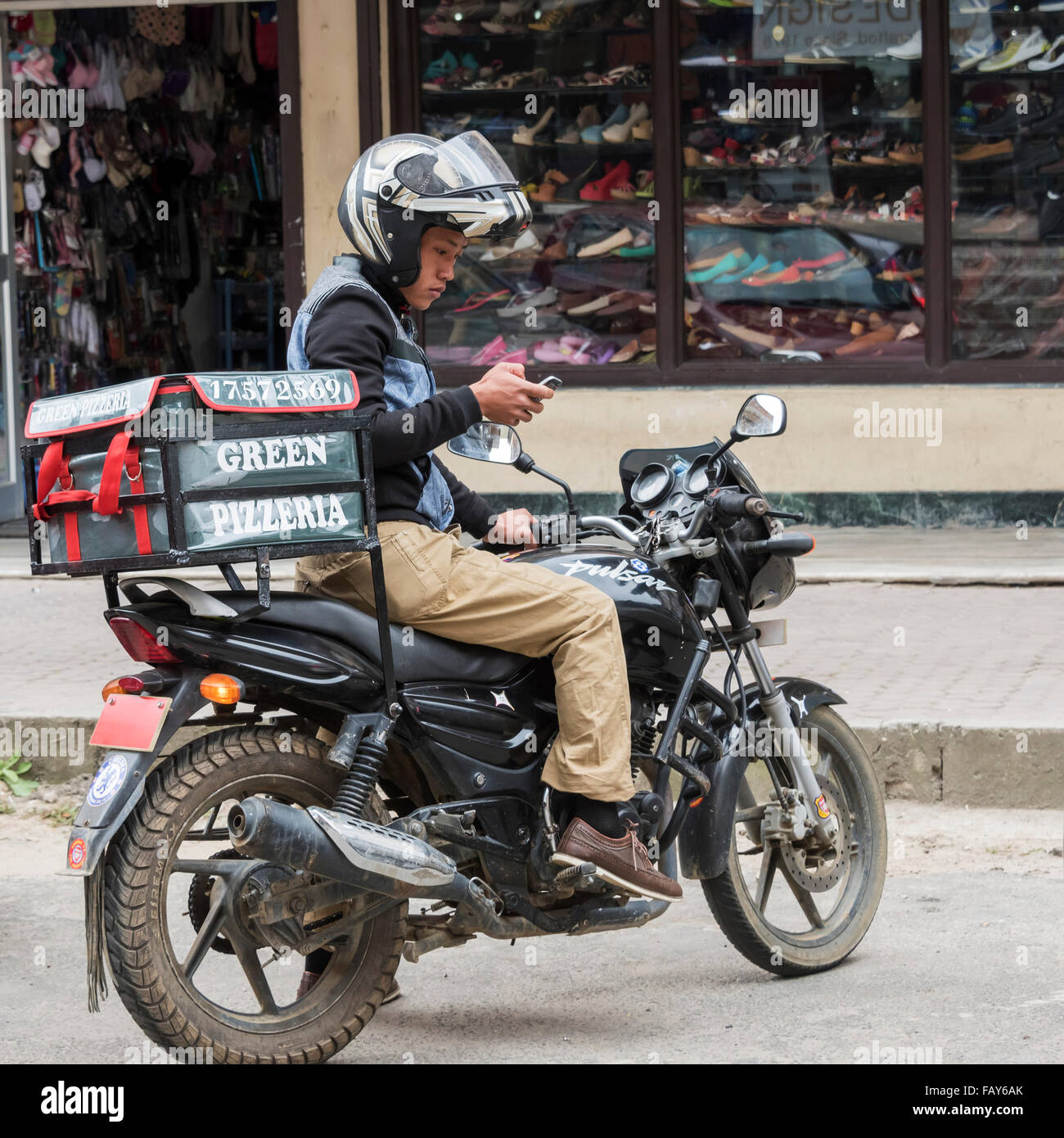 Pizza delivery man on a motorcycle in the street using a smart phone; Thimphu, Bhutan - Stock Image