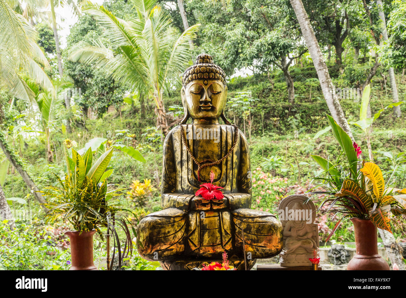 Indonesia, Tejakula, Bali, Hibiscus Flower on Buddha statue - Stock Image