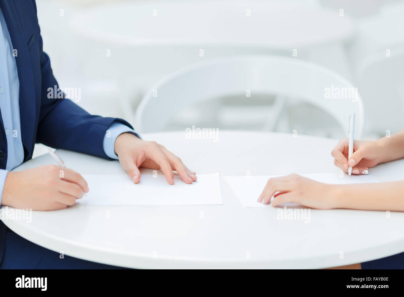 Two colleagues making personal notes. - Stock Image