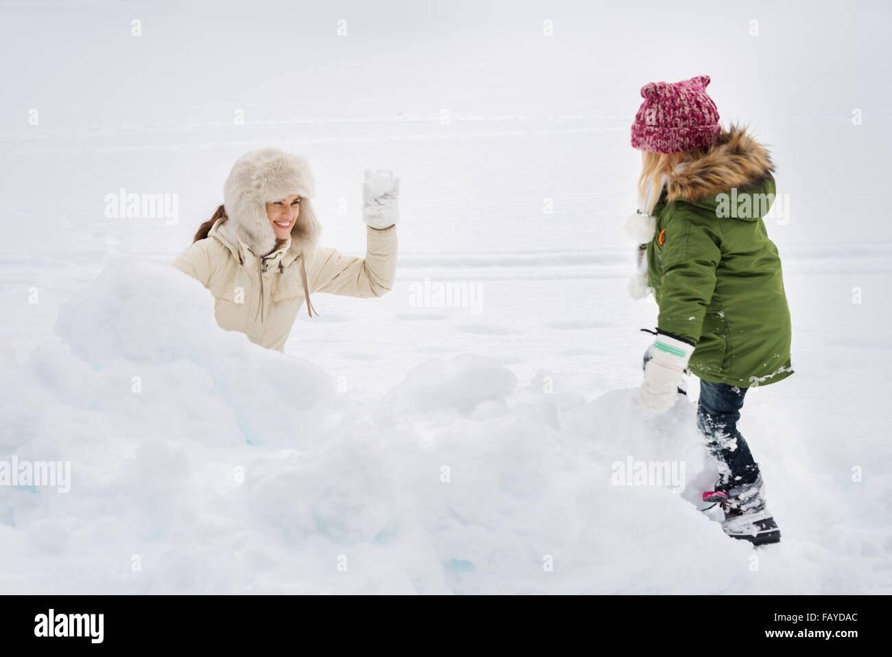 Winter outdoors can be fairytale-maker for children or even adults. Portrait of happy mother and child playing snowball - Stock Image